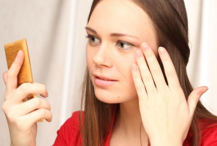 девушка смотрится в зеркальце