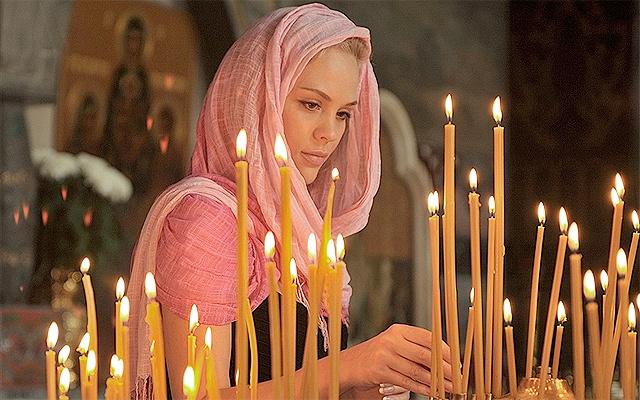девушка ставит церковные свечи