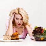 девушка выбирает сладости или салат