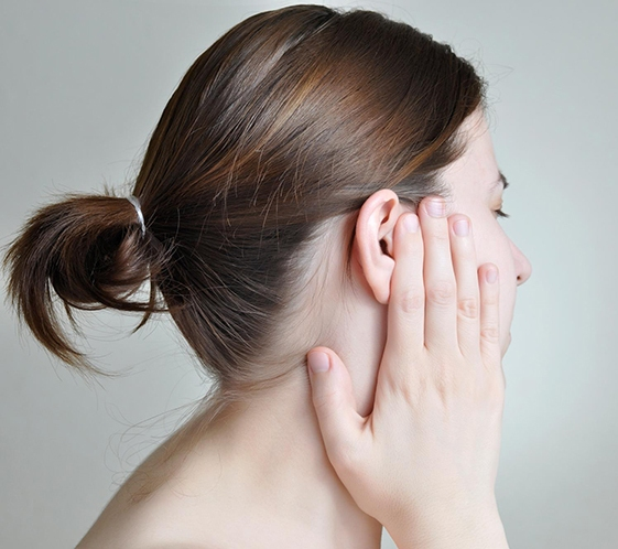 держащаяся за ухо девушка