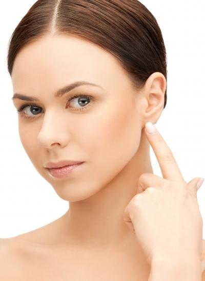женщина указывает на мочку уха
