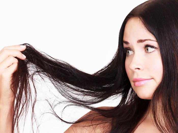 девушка рассматривает свои темные волосы