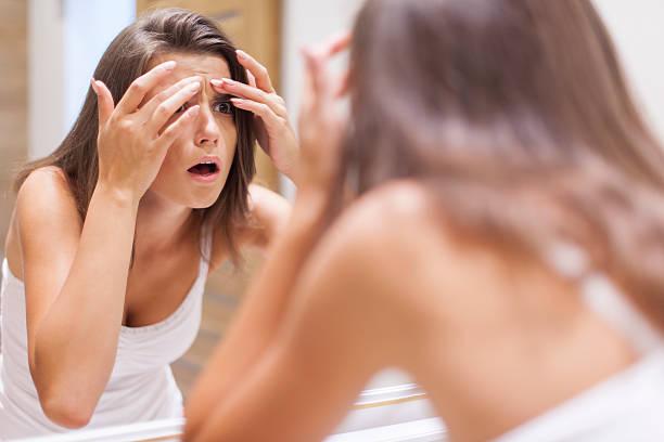 женщина перед зеркалом в ужасе