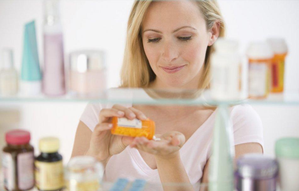 женщина высыпает таблетки на ладонь Витамины от прыщей на лице