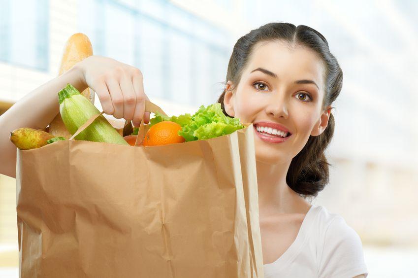 женщина держит овощи в пакете Витамины от прыщей на лице