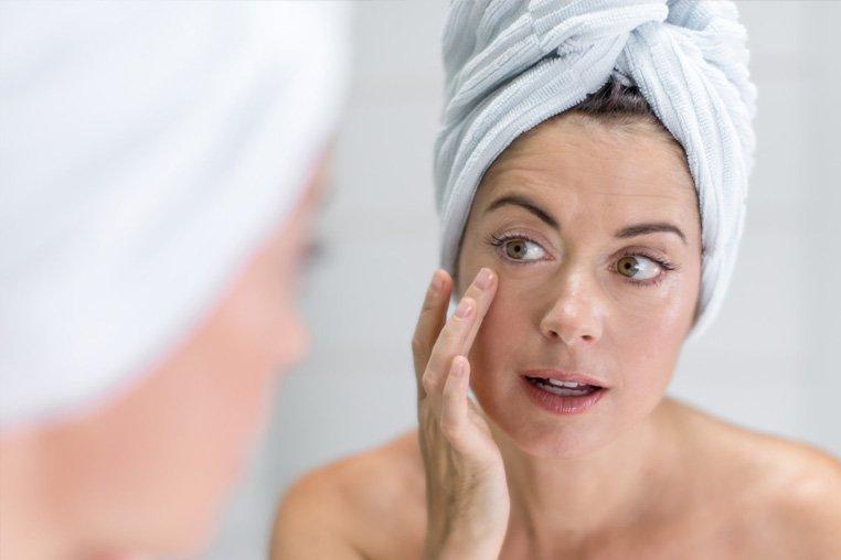 женщина перед зеркалом смотрит на область под глазом