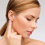 девушка указывает на мочку уха