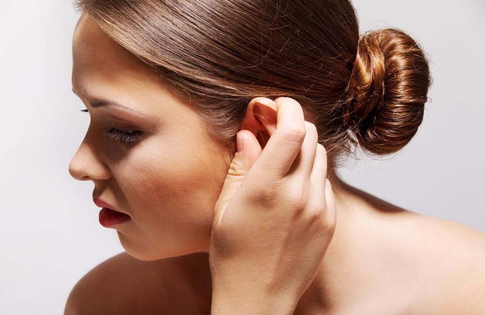 девушка держит свое ухо рукой